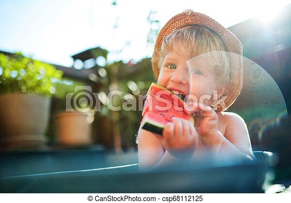 Un niño pequeño con un sombrero en el baño al aire libre en el jardín en verano, comiendo sandía. - csp68112125
