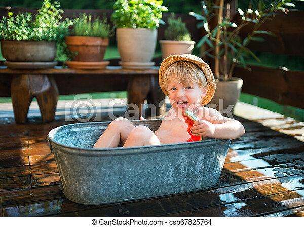 Un niño pequeño con un sombrero en el baño al aire libre en el jardín en verano, comiendo sandía. - csp67825764