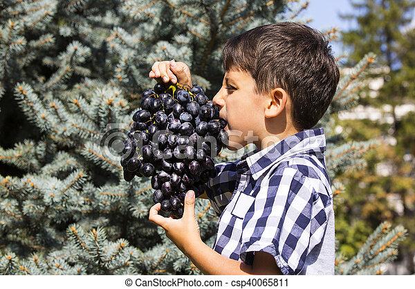 Chico comiendo uvas - csp40065811
