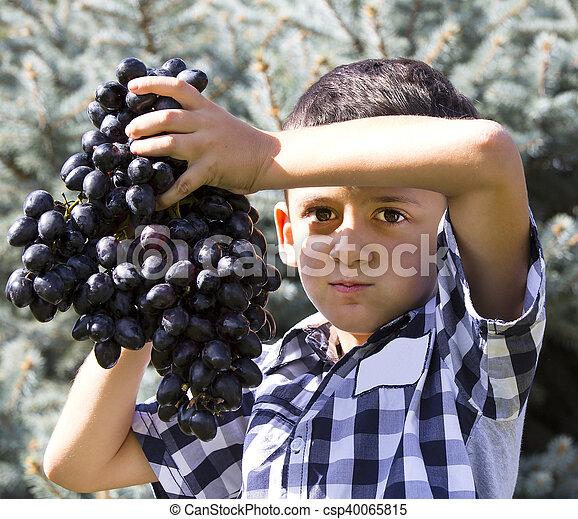 Chico comiendo uvas - csp40065815