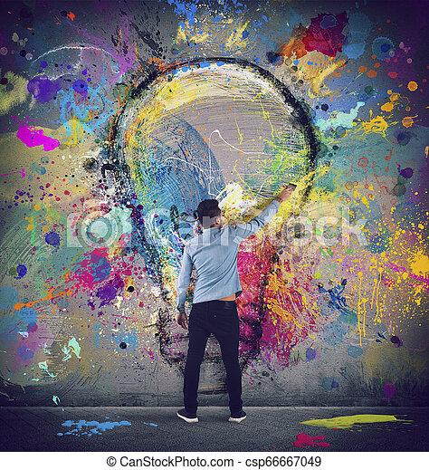 El chico dibuja con un cepillo una gran bombilla. Concepto la innovación y la creatividad - csp66667049