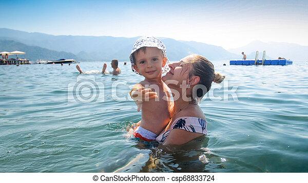 Adorable niño de 3 años nadando en el mar con su madre - csp68833724
