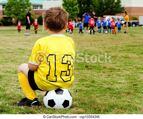 Un chico joven de uniforme mirando el fútbol de la juventud o el fútbol de lado - csp10354345