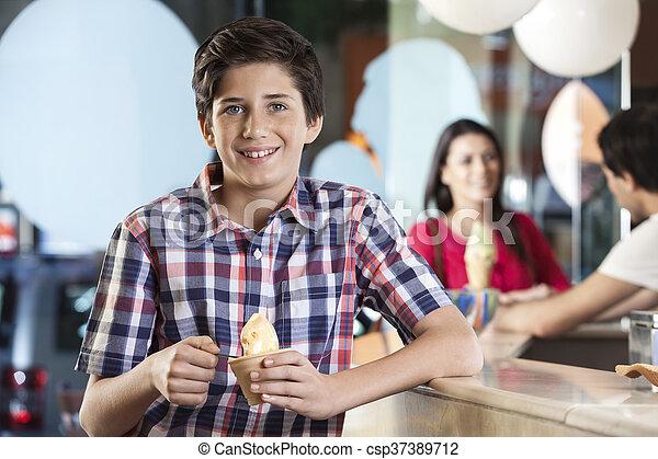 Chico sonriente tomando helado en la sala - csp37389712