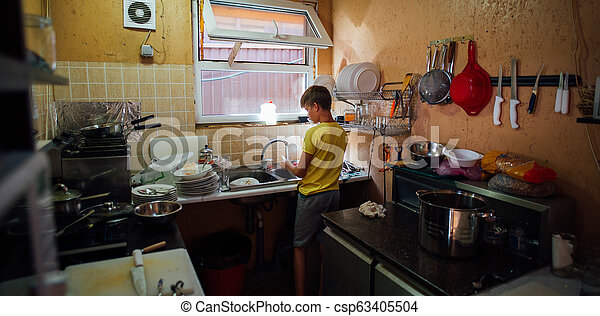Chico lavando platos en la cocina en camiseta amarilla - csp63405504