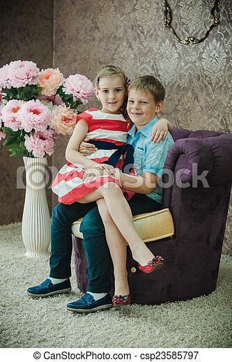 Chico y chica sentados en la habitación agradable - csp23585797