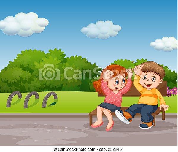 Chico y chica sentados en el parque - csp72522451
