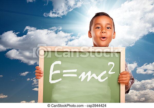 Chico hispano orgulloso sosteniendo una pizarra con la teoría de la relatividad - csp3944424