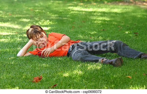 Chico en el parque escuchando mp3 jugador - csp0699372