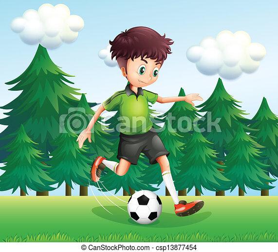 Un chico pateando una pelota de fútbol cerca de los pinos - csp13877454