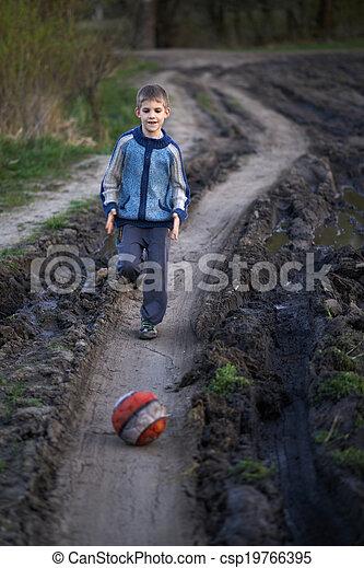 Un chico jugando con una pelota en el camino de lodo - csp19766395