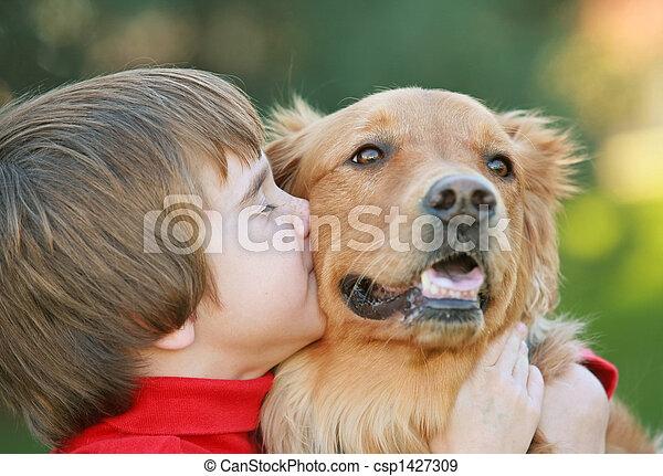 Chico besando perro - csp1427309