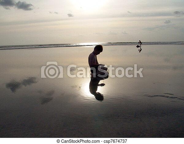 Chico en la playa con Sunset y reflejos - csp7674737