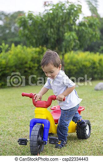Un niño feliz conduciendo su juguete - csp22334443