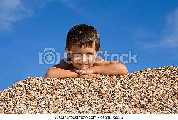 Un chico feliz tirado en las cáscaras y mirando la cámara con sonrisa en el caluroso día de verano - csp4605535