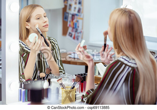 Nice attractive woman looking at her reflection - csp69113885