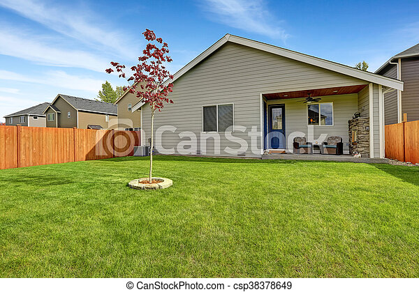 Nice back yard with well kept lawn and view of covered porch with fireplace - csp38378649