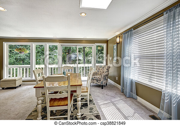 Nice dining room interior with soft blue curtain and floral carpet.