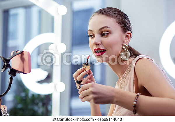 Nice good looking woman applying red lipstick - csp69114048