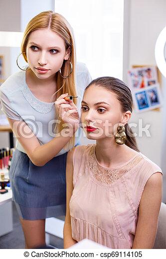 Nice skilled visagiste holding a professional mascara - csp69114105
