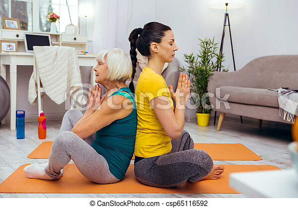 Nice young woman sitting in a lotus pose - csp65116592