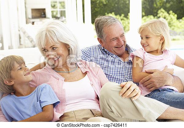 Retrato de abuelos con nietos descansando juntos en el sofá - csp7426411