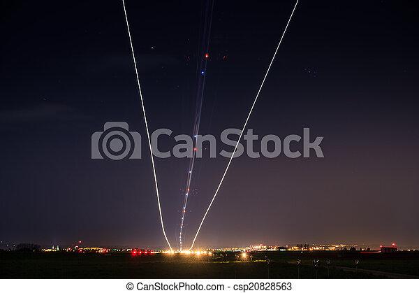 Night airplane landing lights trails stars long exposure