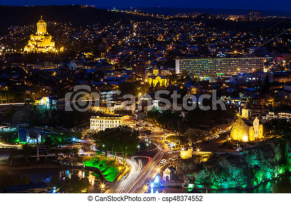 Night panorama view of Tbilisi, capital of Georgia country  Holy Trinity  Cathedral (Sameba) and Metekhi church at night with illumination and moving