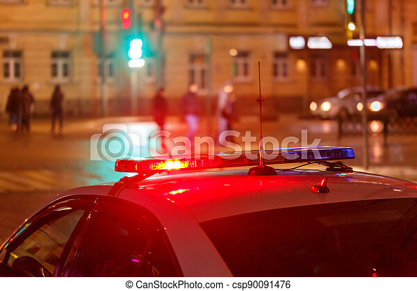 night police car lights in city street with blurry pedestrians crossing road in the background - csp90091476