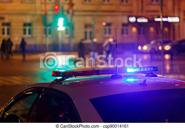 night police car lights in city street with blurry pedestrians crossing road in the background - csp90014161
