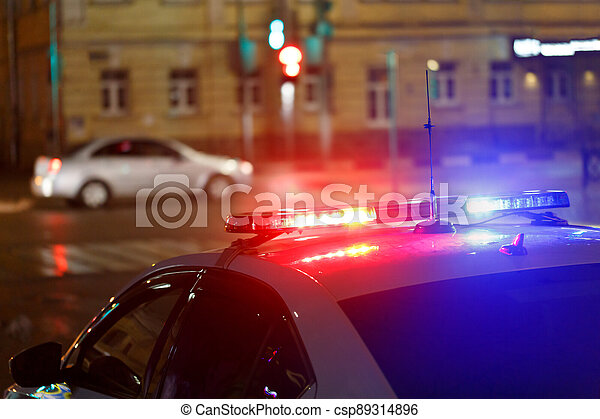 night police car lights in city street with civilian car in blurry background - csp89314896