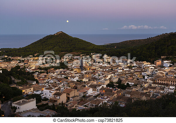 night view of the city of Capdepera from the Castle on the hills towards the sea and full moon - csp73821825