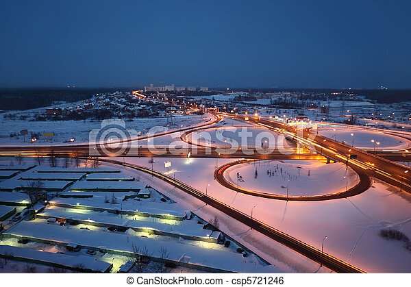 night winter cityscape with big interchange, lighting columns and garages - csp5721246