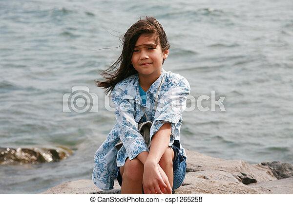 Nine year old girl sitting by lake - csp1265258