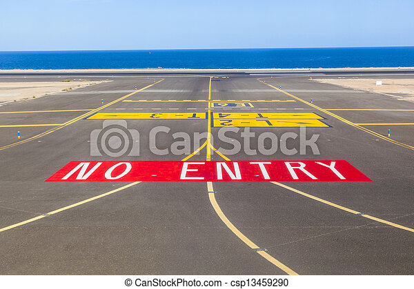 no entry sign at the runway of the airport with ocean in background - csp13459290