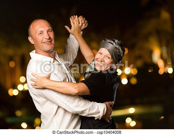 Una pareja de mediana edad bailando vals por la noche - csp10404008