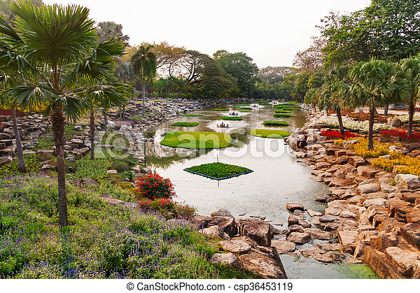 Nong nooch tropical garden in pattaya, thailand. beautiful pond with palm trees.