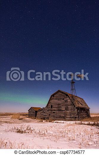 Northern Lights over vintage barn, bins and windmill in Saskatchewan - csp67734577