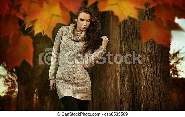 Nostalgic young woman walking in a autumn park - csp6535509