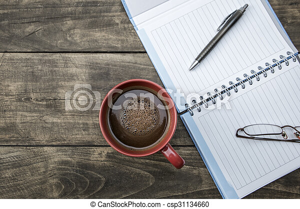 notebook pen and cup of coffee on wood table - csp31134660