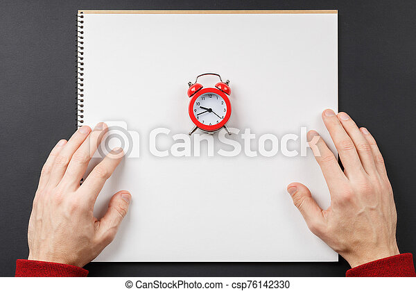 notebook with red alarm clock in hands - csp76142330