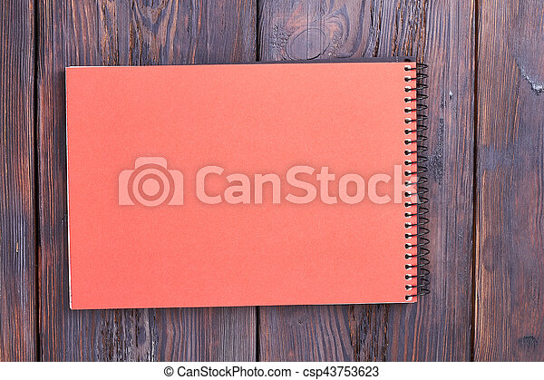 Notebook with spiral on wood. - csp43753623
