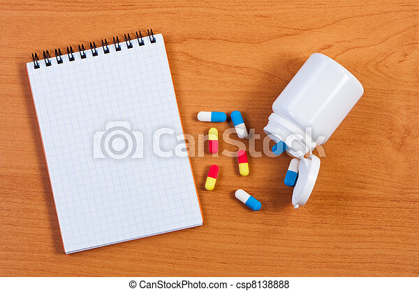 Notebpad and pills on table top view. - csp8138888