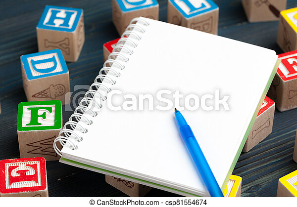 Notepad on wooden table and wood alphabet blocks - csp81554674