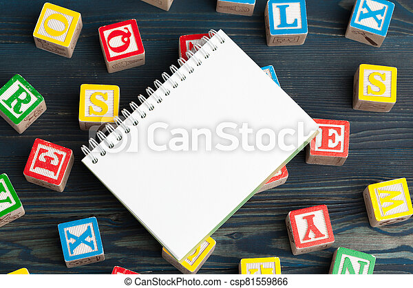 Notepad on wooden table and wood alphabet blocks - csp81559866