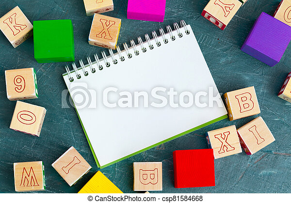 Notepad on wooden table and wood alphabet blocks - csp81584668