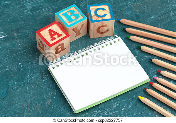 Notepad on wooden table and wood alphabet blocks - csp82227757