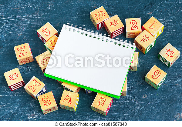 Notepad on wooden table and wood alphabet blocks - csp81587340