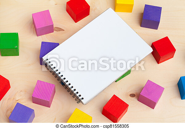 Notepad on wooden table and wood alphabet blocks - csp81558305