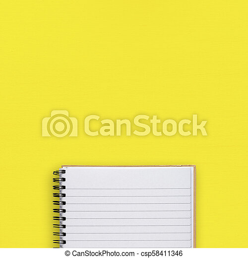 Notepad on yellow background top view - csp58411346